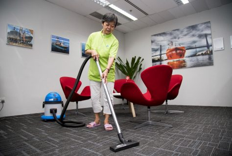 Office auntie vacuuming office carpet floor