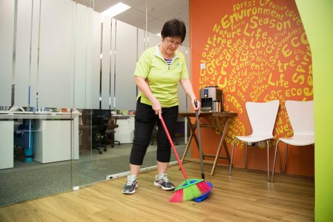 Cleaning aunties sweeping office floor